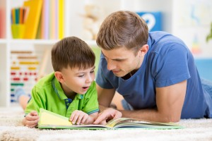 Parent with son and book. Encourage your child to love reading.